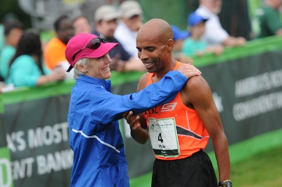 Joan Benoit Samuelson greets Meb at the finish line of the TD Beach to Beacon 10K in 2013.