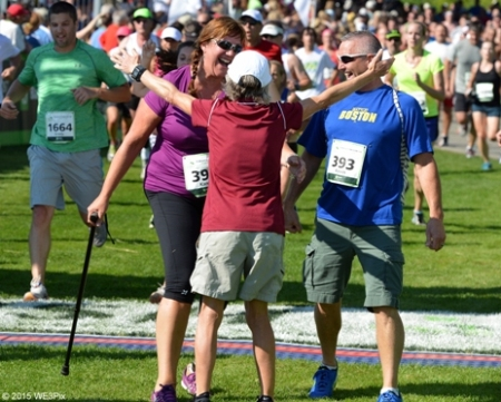 Joan Benoit Samuelson greets Karen Rand McWatters and her husband Kevin at finish of 2015 TD Beach to Beacon 10K. Jason Eggleston photo.